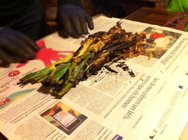 "After the calçots are cooked they are wrapped in newspaper to ""sweat"" for a bit.  Note the heavy duty gloves that Jaume is wearing.  These babies are HOT!"