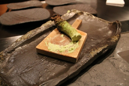 Fresh wasabi being grated on stretched shark skin.