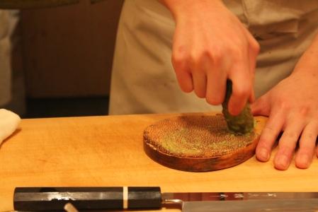 Fresh wasabi being grated on dried sharkskin.